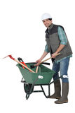 Laborer with wheelbarrow. Laborer stood by a green wheelbarrow Stock Image