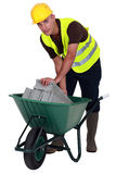 Laborer with a wheelbarrow Stock Images