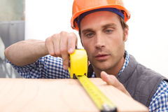 Laborer working with measuring tape Royalty Free Stock Photos