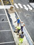 Laborers applying asphalt during the works for the pavement of a. San Sebastian, Spain - October 10, 2018. Laborers applying manually fresh asphalt during the stock photography