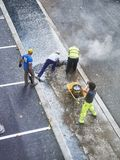 Laborers applying asphalt during the works for the pavement of a. San Sebastian, Spain - October 10, 2018. Laborers applying manually fresh asphalt during the stock images