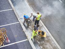 Laborers applying asphalt during the works for the pavement of a. San Sebastian, Spain - October 10, 2018. Laborers applying manually fresh asphalt during the royalty free stock photography