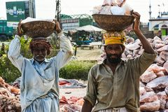 Laborers carrying rock salt. Natural lamps are famous all over the world for their unique beautiful light. These salt lamps emit colorful apricot, yellow & stock photo