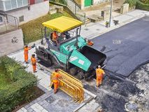 Laborers leveling asphalt during the works for the pavement rehab of a road. San Sebastian, Spain - October 10, 2018. Laborers leveling fresh asphalt with a stock photography