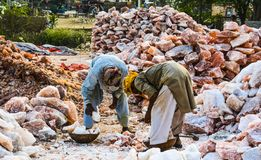 Laborers loading chunks of rock salt. Somewhere near Quaidabad, Khushab.Natural lamps are famous all over the world for their unique beautiful light. These salt stock photography