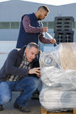 Laborers outside factory unwrapping shipping Stock Photography