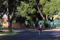 Laborers walk to work in South Africa. Black laborers walk to work through a residential suburb in post-apartheid South Africa as there is no reliable public royalty free stock photo