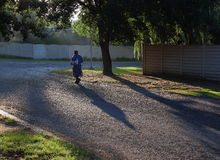 Laborers walk to work in South Africa. Black laborers walk to work through a residential suburb in post-apartheid South Africa as there is no reliable public royalty free stock images
