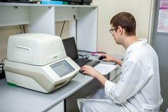 Laborspezialist überprüft die Daten, die auf einem speziellen Apparat für das Analysieren von Proben auf einem Computer erhalten  lizenzfreie stockfotos