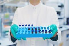 Laborwissenschaftler hält einen Plastikkasten mit Proben der transparenten Flüssigkeit in den Phiolen Stockbild