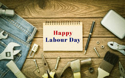 Labour day background concept - Jeans, many handy tools, noteboo. K with happy labour day text , wooden background top view Stock Photos