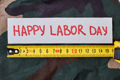 Labour Day card on camouflage. Greeting paper and tape measure. Preparing for holiday Royalty Free Stock Image