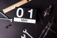 Labour day. May 1st. Day 1 of may month, calendar on black background with workers tools.  royalty free stock photos