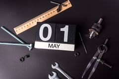 Labour day. May 1st. Day 1 of may month, calendar on black background with workers tools.  stock image