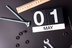 Labour day. May 1st. Day 1 of may month, calendar on black background with workers tools.  stock images
