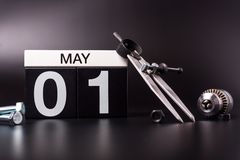 Labour day. May 1st. Day 1 of may month, calendar on black background with workers tools.  royalty free stock photo