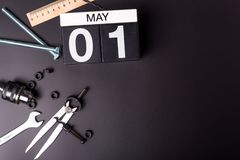 Labour day. May 1st. Day 1 of may month, calendar on black background with workers tools with empty space for text.  stock images