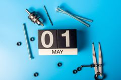 Labour day. May 1st. Day 1 of may month, calendar on blue background with tools.  royalty free stock photos