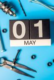 Labour day. May 1st. Day 1 of may month, calendar on blue background with tools.  stock photo