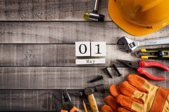 Labour Day, Wooden Block calendar with many handy tools on wooden background texture.  stock images