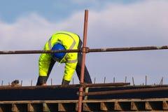 Labour med den blåa hjälmen som sticker stänger för metallstänger in i ramförstärkningen arkivbild