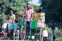 Labour in Siliguri. SILIGURI, INDIA – DECEMBER 5, 2016: three-wheeled cart is widely used for transport of produce from a wholesale market in Siliguri Stock Image