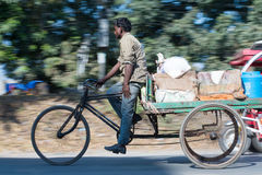 Labour in Siliguri. SILIGURI, INDIA – DECEMBER 5, 2016: three-wheeled cart is widely used for transport of produce from a wholesale market in Siliguri Stock Photo