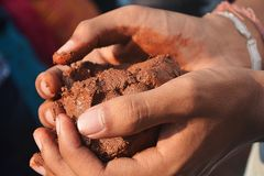 Labour working with mud ahead of labour day. Close up of a labour working with mud ahead of labour day and may day celebrations in India stock image