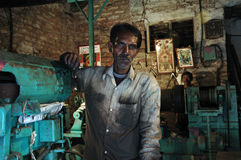 Labourer. A labourer is working with a machine in a small factory in a slum area of India Royalty Free Stock Photos