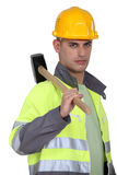 Labourer carrying a mallet Stock Photo