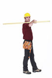 Labourer carrying a  plank Royalty Free Stock Images