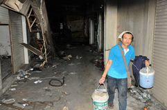 Labourer at work in a fire gutted mall in Bangkok. BANGKOK - MAY 23: Labourer at work in the fire damaged interior of a shopping mall at Siam Sqaure in the Stock Images