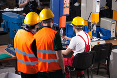 Labourers in factory. Three labourers in safety helmets are working in factory Royalty Free Stock Image