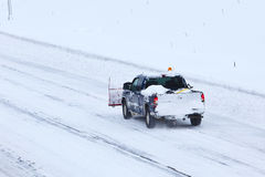 Labourez les camions sur la route après la tempête 2013 de neige Photographie stock