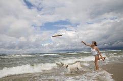 Labrador retriever playing on the beach. Young girl playing with labrador retriever on the beach Stock Photo