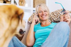 Labrador sits in front of a mature woman who is phoning royalty free stock photo