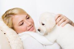 Labradorvalp som ligger på kvinnan royaltyfri fotografi