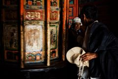 tibetan buddhist pilgrims turning a large prayers wheel inside the temple royalty free stock image