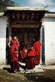 young tibetan buddhist monks waiting outside of their school below the towering mountains stock photography