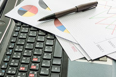 Labtop , financial charts , Document file , pen on the table Stock Photography