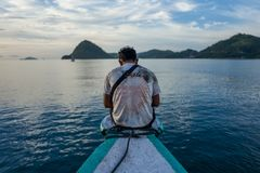 Labuan Bajo, Indonesia - April 01, 2018: Local man on boat in Labuan Bajo harbour stock images