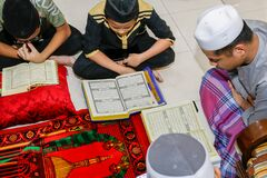 Malaysian muslim kids reading the book of the holy Quran to celebrate the holy Ramadan Kareem feasting