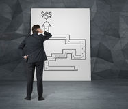 Labyrinth to money. Businessman looking for a way out of labyrinth to money Stock Image