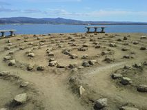Labyrinthe par la mer avec des bancs images stock