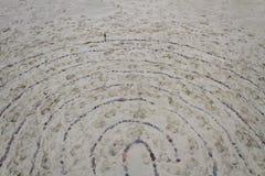 Labyrinthe sur le sable fait de pierres Photographie stock libre de droits