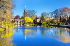 Lac à Bruges, en Belgique, église et réflexion médiévale de maisons dans l'eau photo stock
