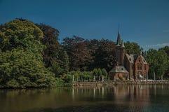 Lac étonnant entouré en la verdure et le vieil immeuble de brique de l'autre côté à Bruges Photographie stock