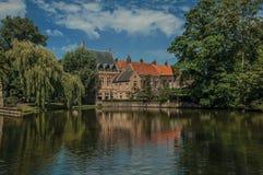 Lac étonnant entouré en la verdure et le vieil immeuble de brique de l'autre côté à Bruges Image stock