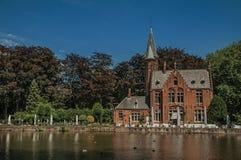 Lac étonnant entouré en la verdure et le vieil immeuble de brique de l'autre côté à Bruges Image libre de droits