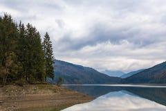 Lac alpin avec les arbres se reflétants et beau ciel nuageux en automne Images stock